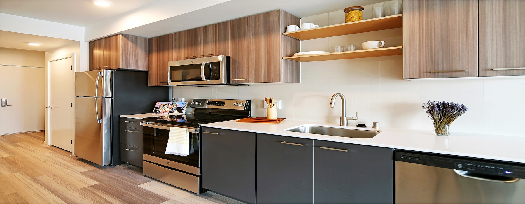well lit furnished kitchen area with modern wood cabinets and stainless steal appliances